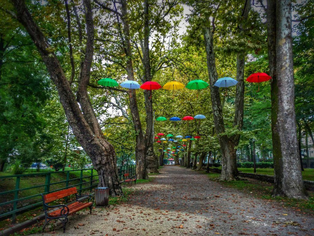 Park in Bihać met parapluus tussen de bomen
