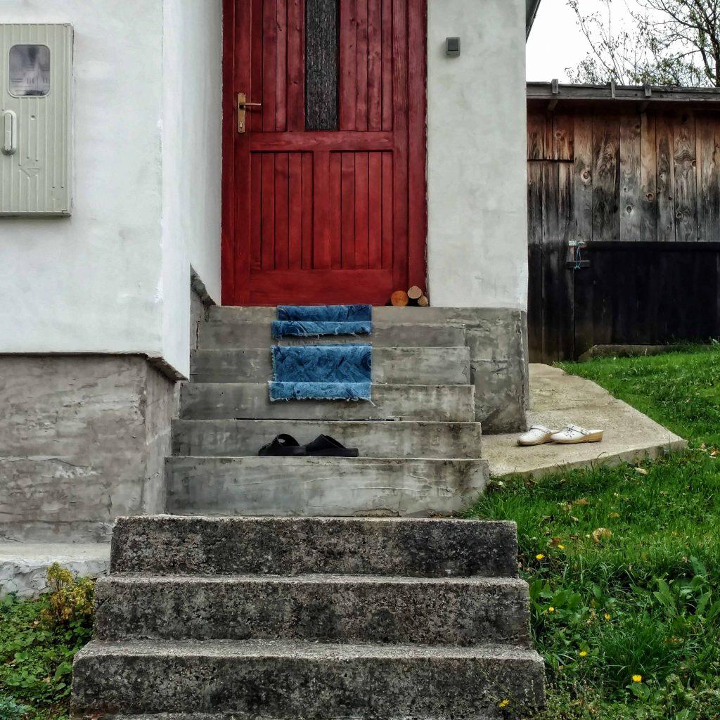 Huis langs de weg van Una National Park naar Martin Brod, tapijt over de trap
