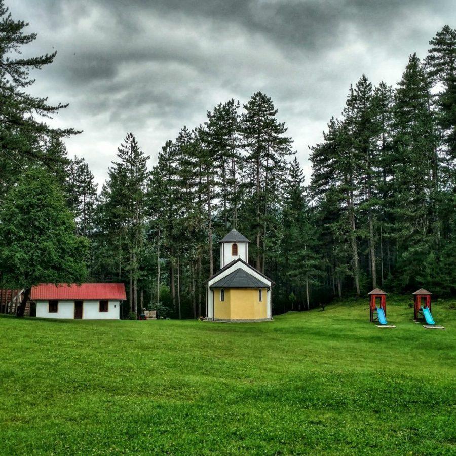 Kerkje met grasveld en picknicktafel middenin de bossen